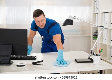 Mid adult male worker cleaning desk with sponge at office