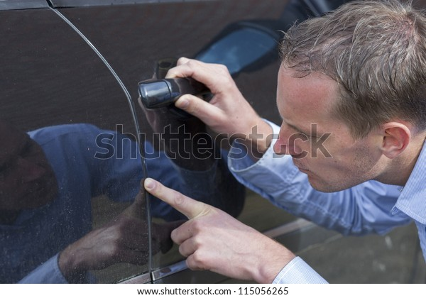 Mid adult man checking his car for scratches and dents. Horizontal shot.