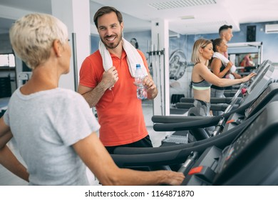 Mid adult man having chat with frend after hardly training on treadmill machine in the gym.