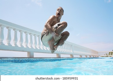 Mid adult man jumping into swimming pool