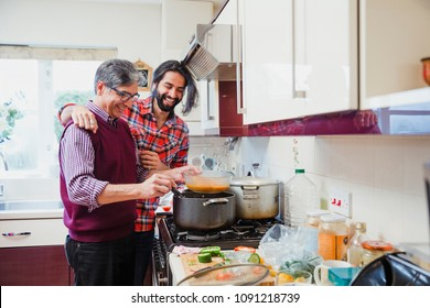 Mid adult man is looking over his father's shoulder as he prepares a curry at home.