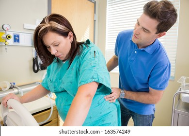 Mid adult man looking at pregnant wife while massaging lower back