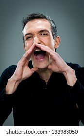 Mid Adult Man Shouting Over a Grey Background