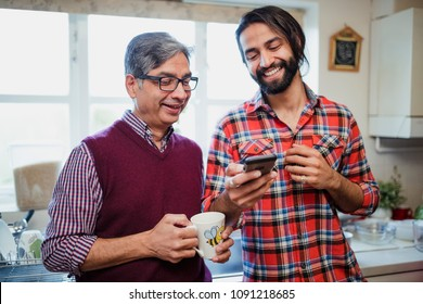 Mid adult man is showing his mature father something on his smart phone. He is holding a mug of tea.