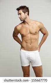 Mid adult man in underpants looking away, studio shotv