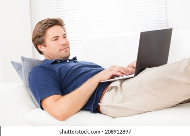 Mid adult man using laptop while resting on sofa at home
