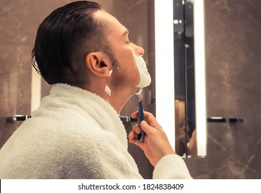 Mid adult man using razor and shaving in the bathroom.
