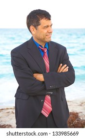 Mid adult mixed race businessman looking away while standing arms crossed with sea in background. Vertical shot.