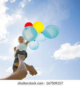 Mid adult mother lifting daughter holding colorful helium balloons against cloudy sky