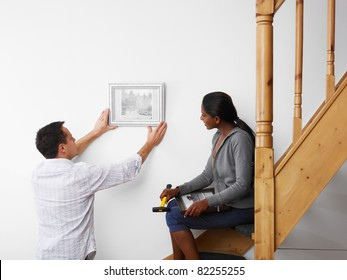 mid adult multiethnic couple hanging pictures to the wall and smiling. Horizontal shape, copy space