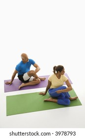 Mid adult multiethnic man and woman sitting and stretching on exercise mats.