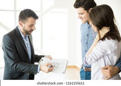 Mid adult realtor showing blueprint to couple in new luxury apartment