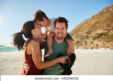 Mid adult white couple standing on a beach, dad carrying son on his shoulders, front view, close up