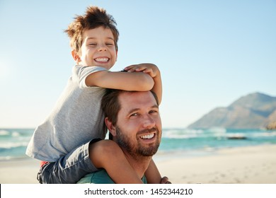 Mid adult white man on a beach with four year old son on his shoulders, looking to camera, close up
