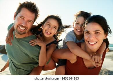 Mid erwachsene weiße Eltern, die ihre Kinder an einem Strand schwingen, mit Kameralächeln, Nahaufnahme, Hintergrundbeleuchtung