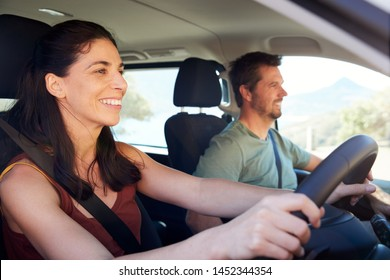 Mid adult white woman driving car, husband beside her in front passenger seat, close up, side view