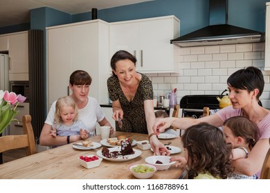 MId adult woman handing a slice of cake to a little girl sat at the dining table. There are two other mid adult women sat at the table with their children enjoying the sweet treats.