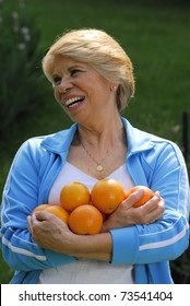 Mid adult woman holding fresh oranges.