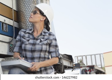 Mid adult woman inspecting timber truck