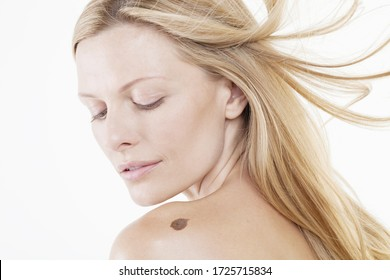 Mid adult woman looking at mole on shoulder, studio shot