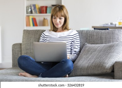 Mid adult woman on her sofa using laptop at home.
