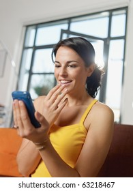 mid adult woman sitting on sofa, getting good news on mobile phone. Vertical shape, side view, waist up