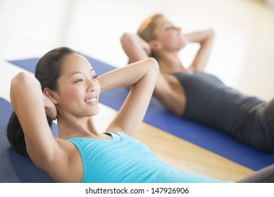 Mid adult woman smiling while doing sit-ups at gym with female friend in background