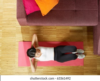 mid adult woman training abdominals at home. Horizontal shape, full length, high angle view, copy space