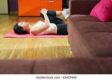 mid adult woman training abdominals at home. Horizontal shape, three quarter length, side view, copy space