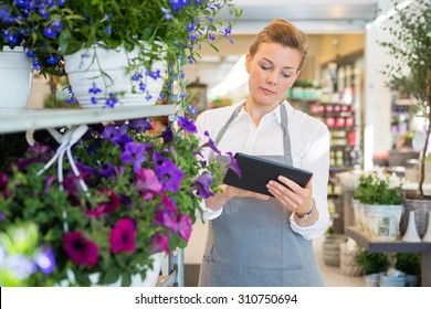 Mid adult woman using digital tablet while standing by trolley in flower shop