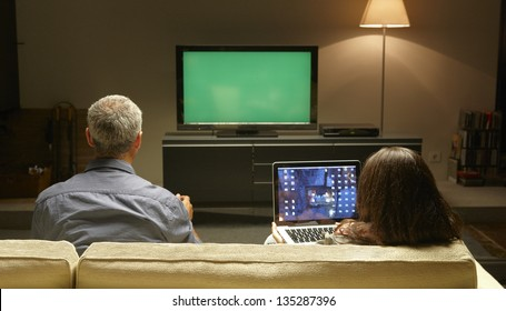 Mid Adults watching TV and PC thanks to Internet possibilities