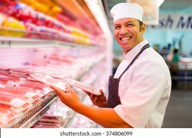 mid age butcher organizing meat products in butchery