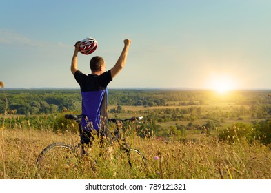 Mid age Male cyclist shows raised up hands gesture on the top of the hill