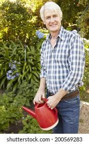 Mid age man watering garden
