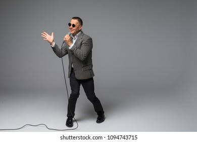 The mid age Showman interviewer with emotions. Young elegant mature man holding microphone against white background.