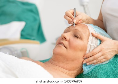 Mid age woman with correction mark for plastic surgery