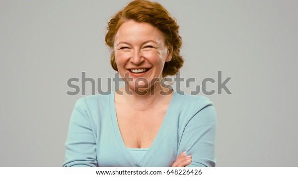 Mittlere Schauspielerin zeigt Freudengefühle. Schauspielerin im Studio zeigt das Gefühl der Freude. Nahaufnahme eines Porträts von Akumen in hellblauem Pullover. Schauspielerin mit lockig rotem Haar zeigt das Gefühl der Freude