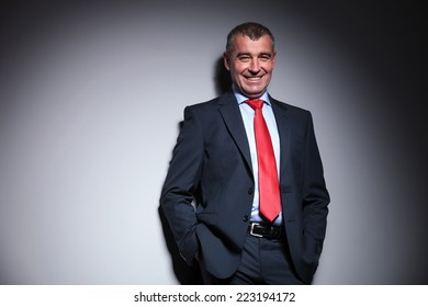 Mid aged business man smiling while holding his hands in pocket, leaning on a grey wall