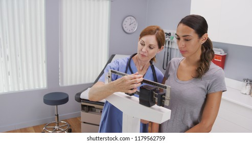 Mid aged caucasian nurse weighing female patient on scale
