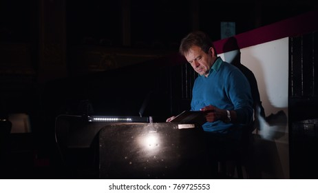Mid aged conductor alone in dark orchestra pit studies sheet music and tweets the tune. Camera moves from right to left. Indoor. Medium