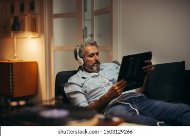 mid aged man listening music with headphones ,playing music on record player relaxed in sofa at his home