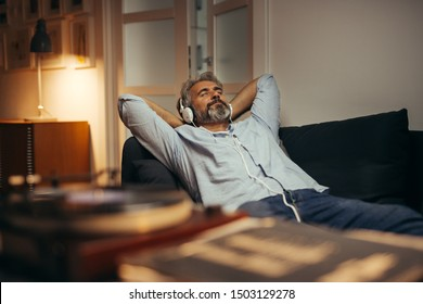 mid aged man listening music with headphones on phonograph, relaxed in sofa at his home - Shutterstock ID 1503129278