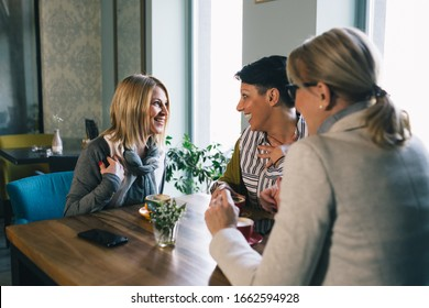 mid aged woman friends enjoying time drinking coffee in cafe