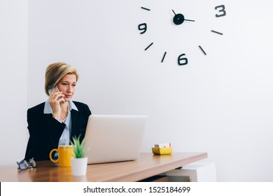 mid aged woman sitting desk at her office and talking on mobile phone