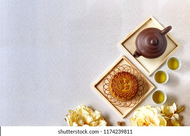 Mid Autumn festival. Moon cake and tea isolated with white texture background.Moon cake Chinese text translation:Single yolk salty