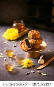 Mid autumn festival mooncake and Chinese tea on moody table top background.