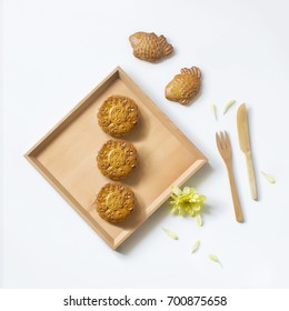 "Mid autumn festival mooncake and wooden eating utensils on white background. Flat lay image. Translation text on mooncake ""mid autumn""."