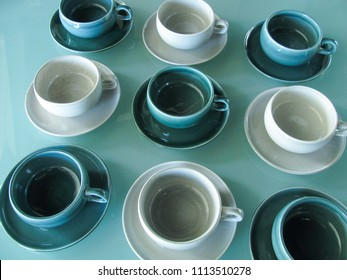 Mid century modern coffee cups and saucers in blue and gray on a glass table with a retro vintage look
