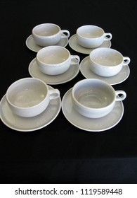 Mid century modern gray coffee cups and saucers on a black limbo background with a retro vintage look, vertical format