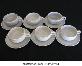 Mid century modern gray coffee cups and saucers on a black limbo background with a retro vintage look